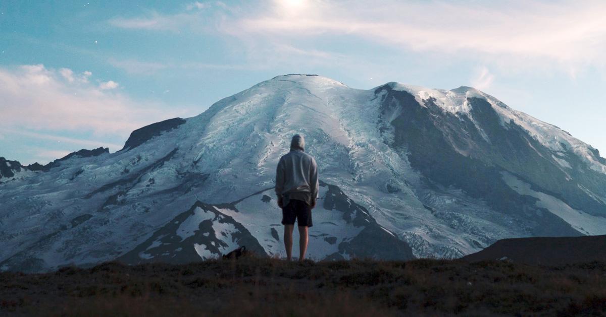 パーカーと半ズボンの男性が背を向け、険しい雪山に対峙する写真